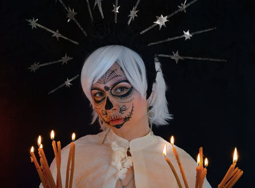 Young female magician with face art and burning candles in hands in black studio