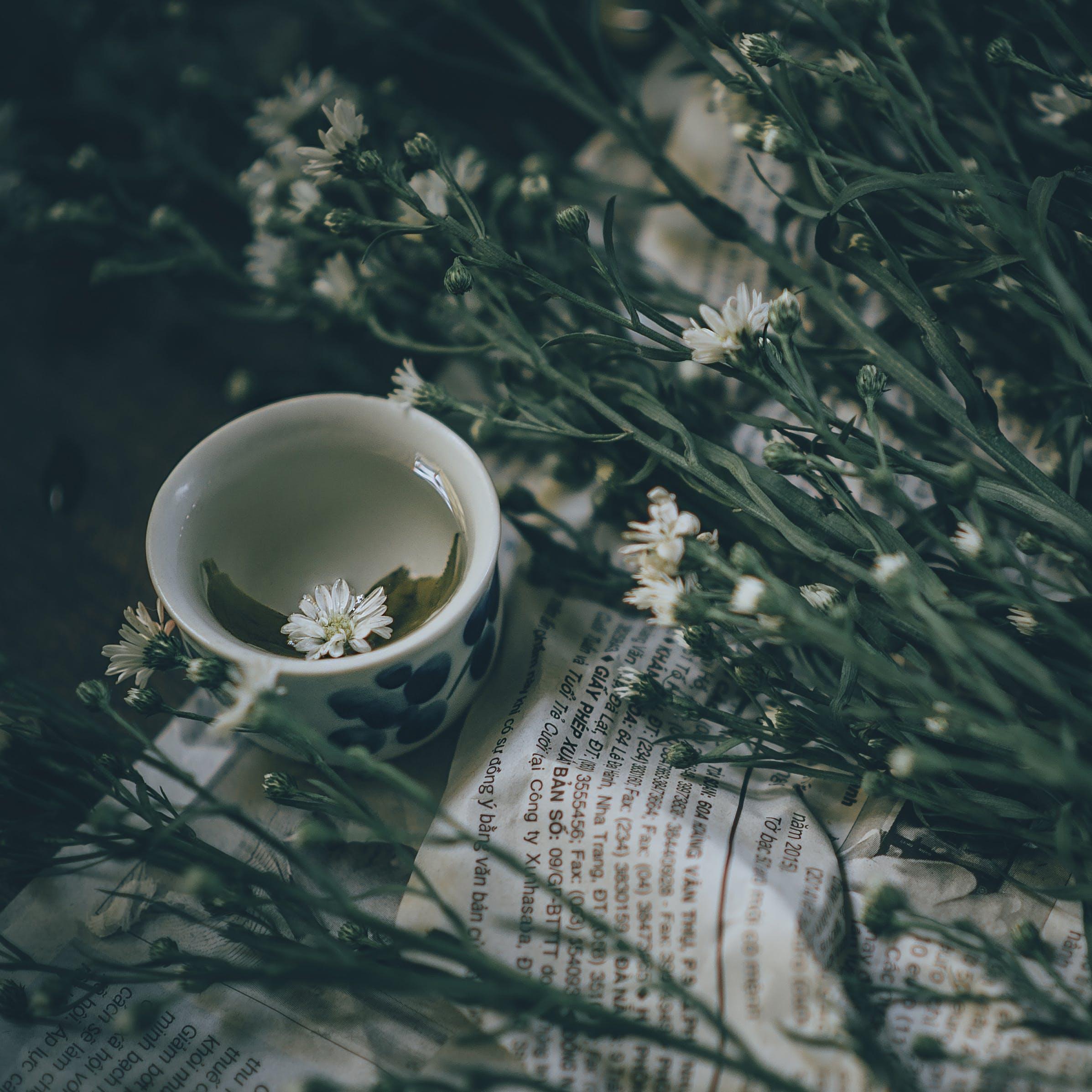 White Ceramic Mug Beside White Petal Flower