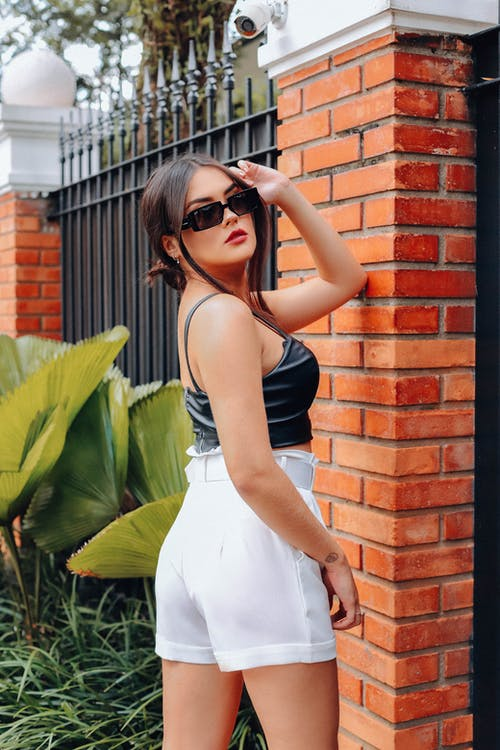 Woman in Black Tank Top and White Skirt Wearing Black Sunglasses Standing Beside Brown Brick Wall