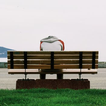 Person Wearing Grey and Orange Hoodie Sitting on Brown Wooden Park Bench during Daytime