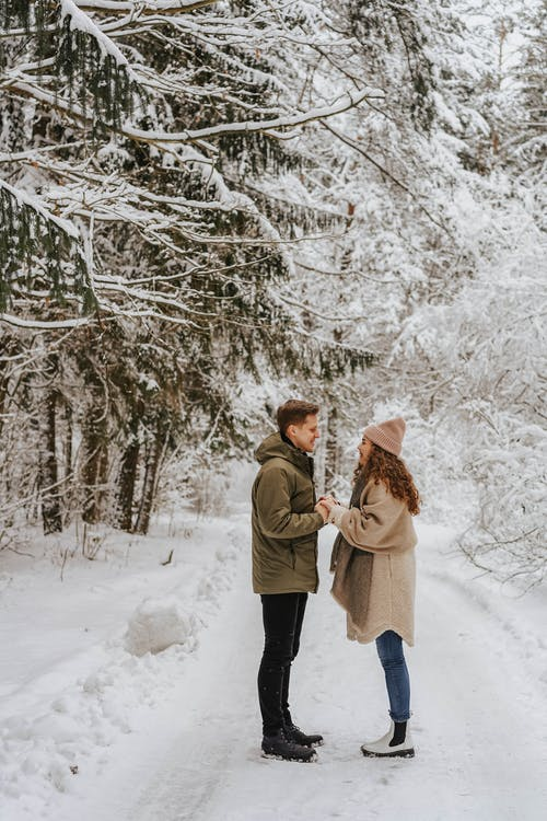 Couple Facing Each Other Under Snow Covered Trees