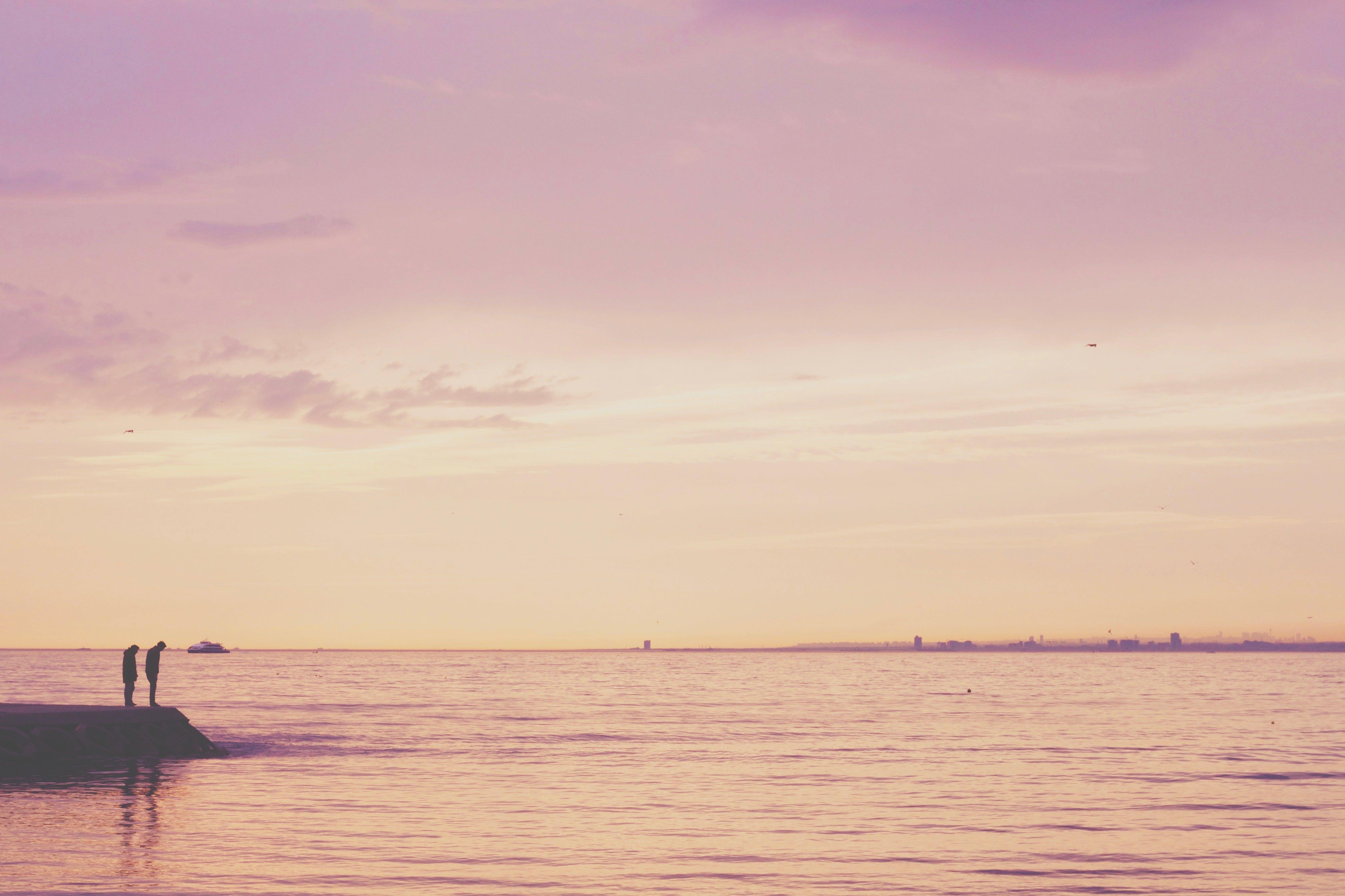 2 Person Standing on Shore Near Calm Sea