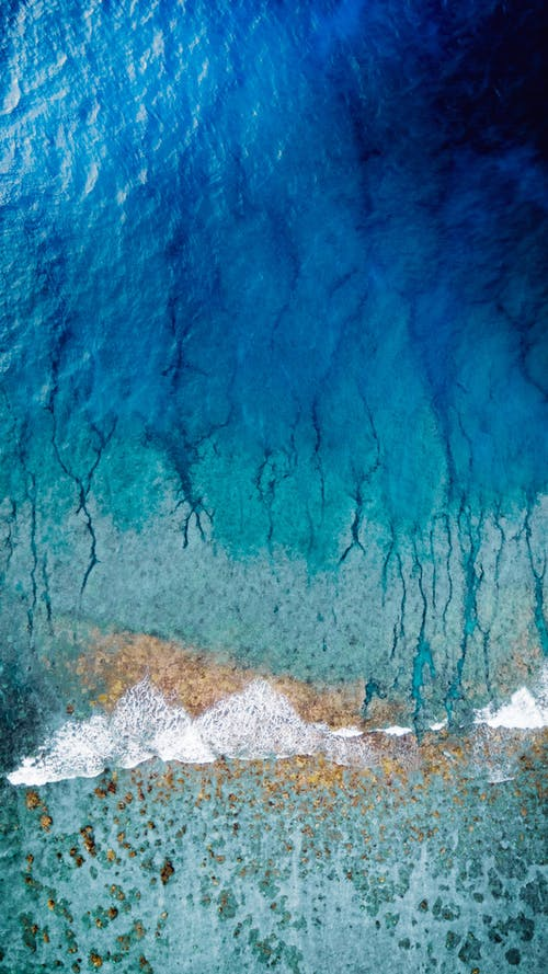 Abstract background of light blue splashes on coastline and bright azure water surface mixing with stains of paint