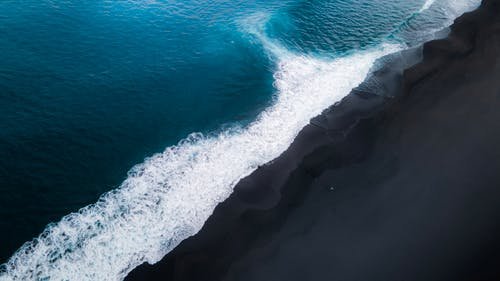 Drone view of powerful sea with clean azure water and foamy waves crashing on beach in tropical country in nature