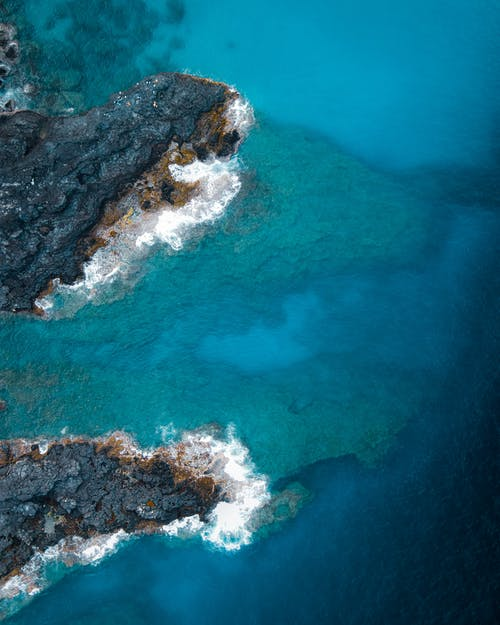 Drone view of seascape with rough stony formations with uneven surface located among azure sea in nature in tropical country