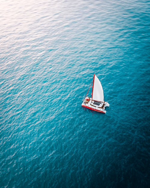 Sailboat floating on rippling sea