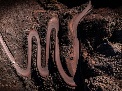 Top view of narrow winding roadway with cars running through dry land with tall rough rocky formations in wild nature