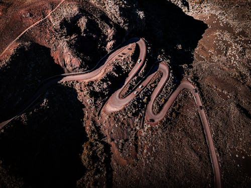 Drone view of cars riding on curvy roadway near tall rocky cliff in dry terrain with boulders in wild nature