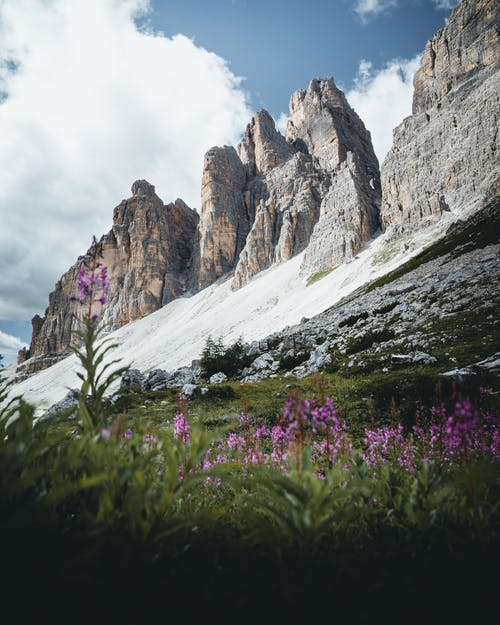 Scenic view of rough cliff ridge located near lush flowering valley under blue sky in sunny nature