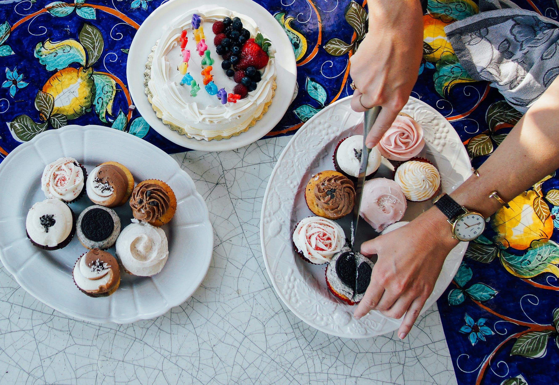 Person Slicing Cupcake on White Ceramic Plate