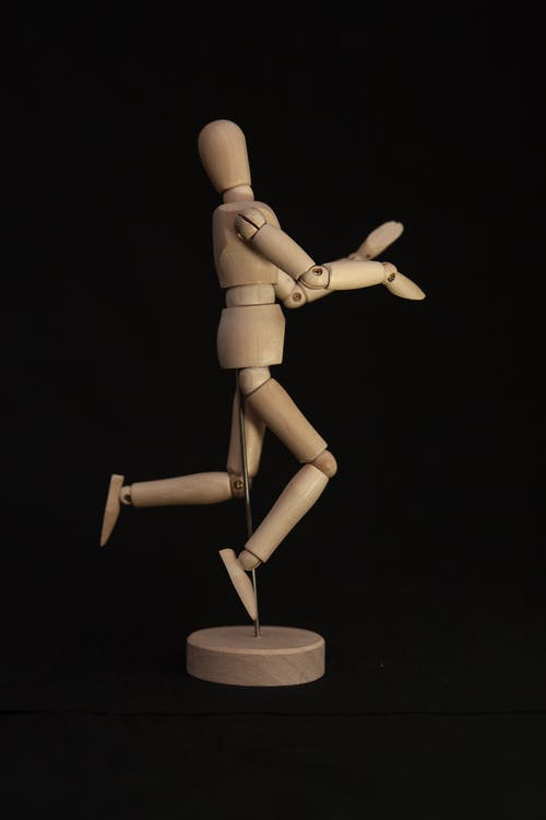 Brown Wooden Human Figure on Black Table