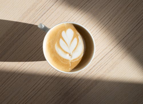 Cup of delicious latte with decor on froth