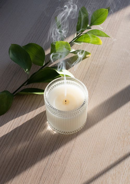From above of wax candle with vapor near green plant sprig on desk with shades