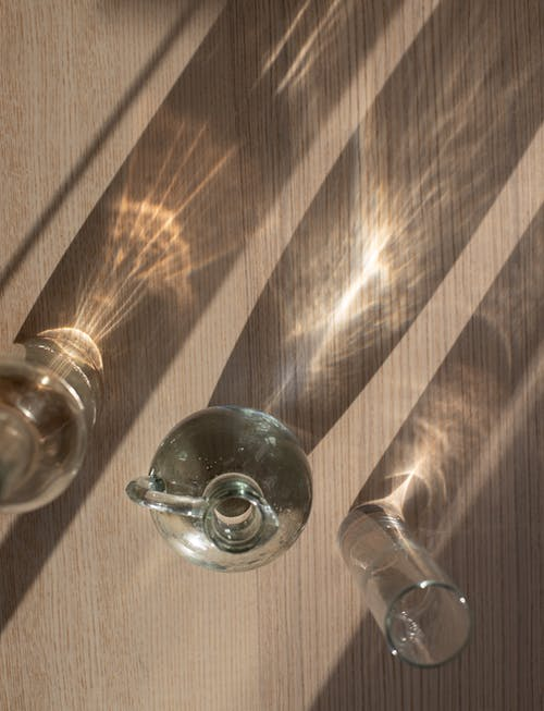 Assorted glassware on shiny table with shadows