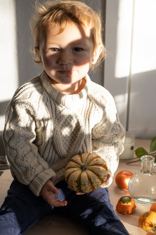 Adorable little child with blond hair in stylish knitted sweater sitting on wooden table with fresh small pumpkin in hand and looking at camera