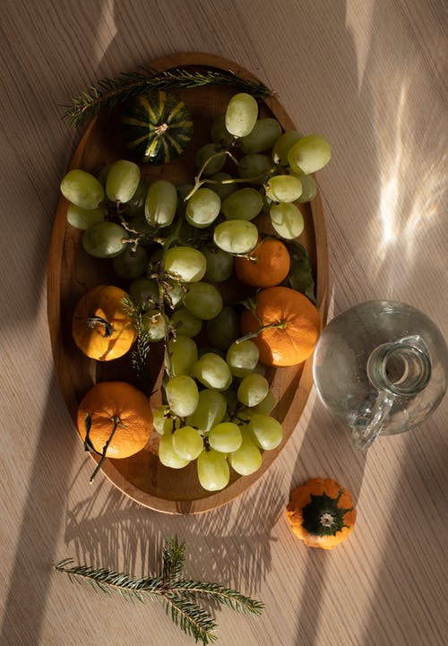 Top view of fresh green grapes and tangerines arranged in wooden plate and placed on table near glass jar and fir twig in sunlight