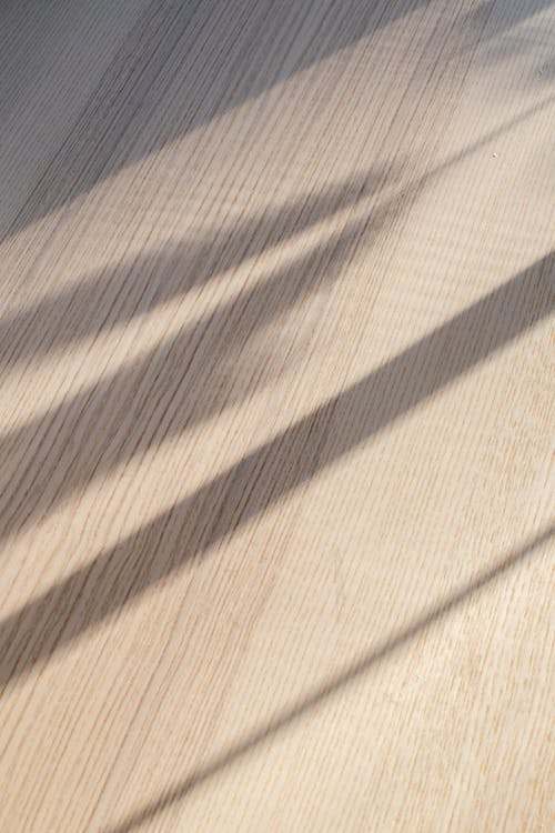 From above of curtain shadow on wooden floor in room on sunny day