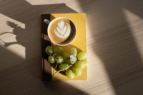 From above of fresh ripe green grapes and cup of fresh foamy cappuccino with latte art placed on book on wooden table in sunlight at home