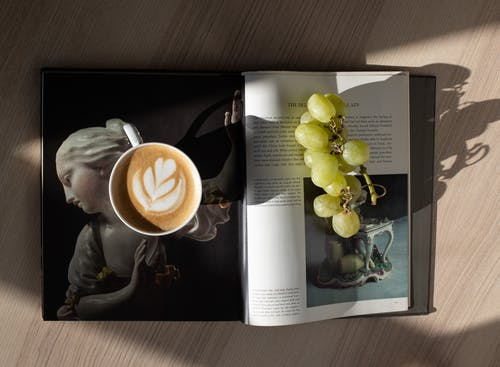 Top view of cup of fresh brewed cappuccino with latte art and bunch of healthy green grapes placed on opened magazine on wooden table