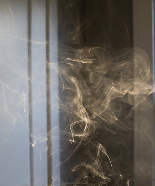 Swirling thick smoke of cigarette forming chaotic figures in dark room in apartment