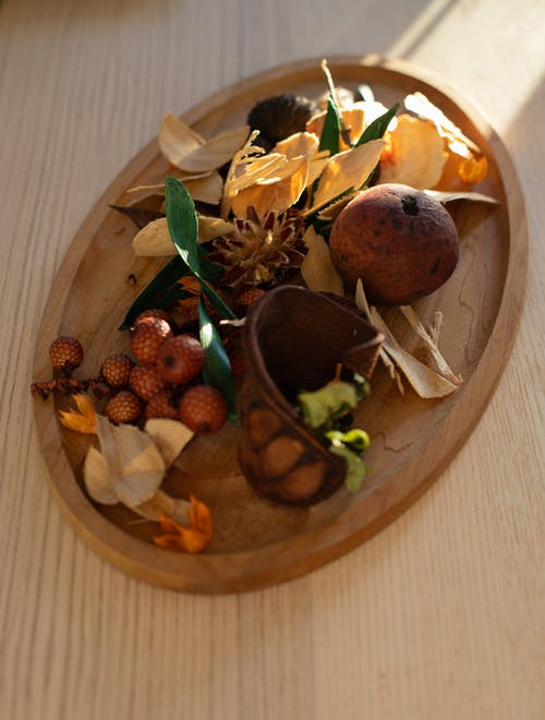 From above of exotic rattan and sapodilla fruits composed with flower petals on wooden plate placed on table in daylight