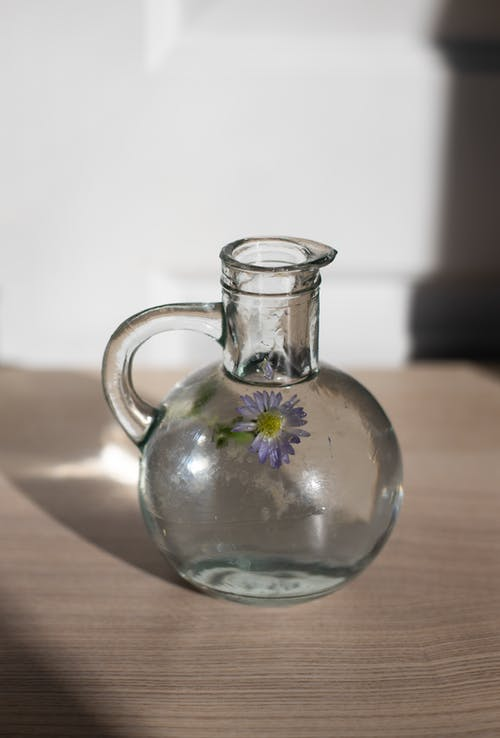 Clear Glass Pitcher on Brown Wooden Table