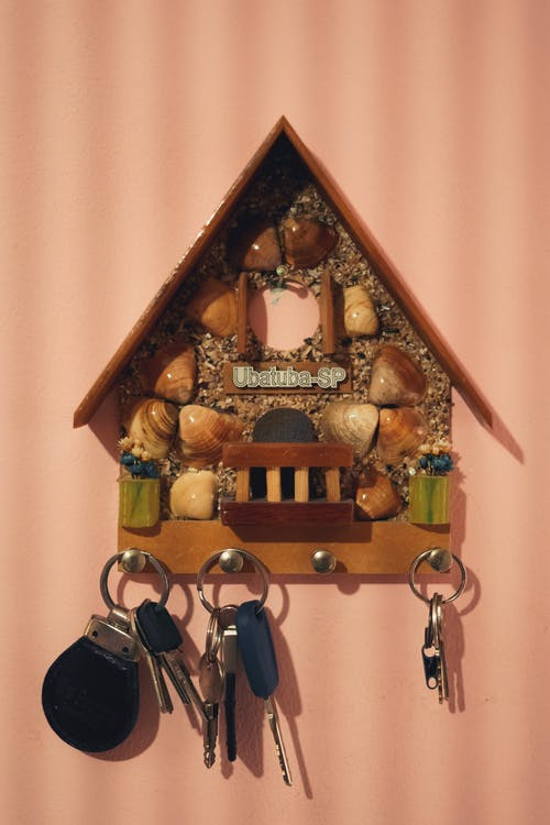 Timber decorative retro house with seashells and hanging keys on pink wall with stripes
