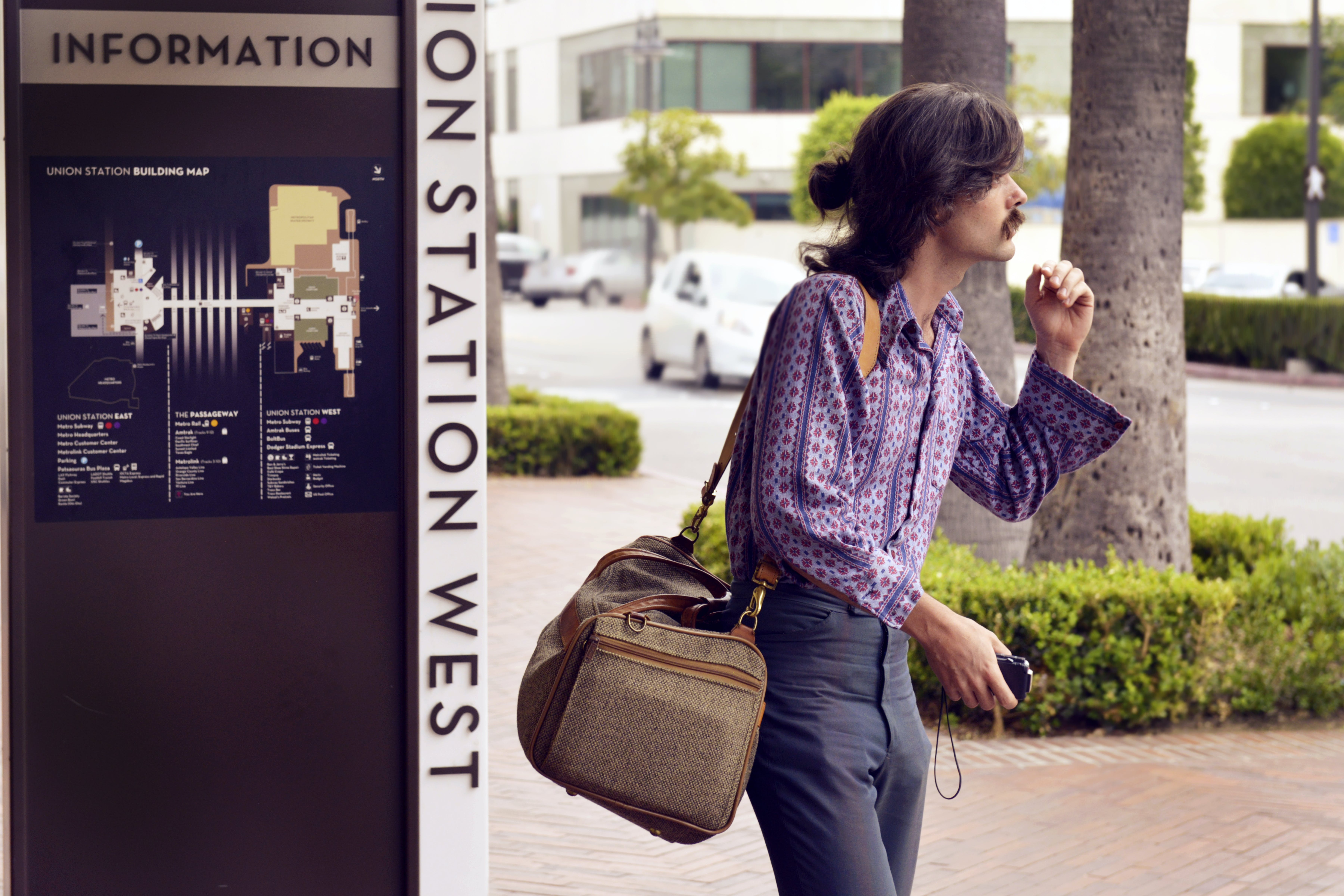 Person Wearing Purple Dress Shirt and Black Pants White Carrying Brown Sling Bag
