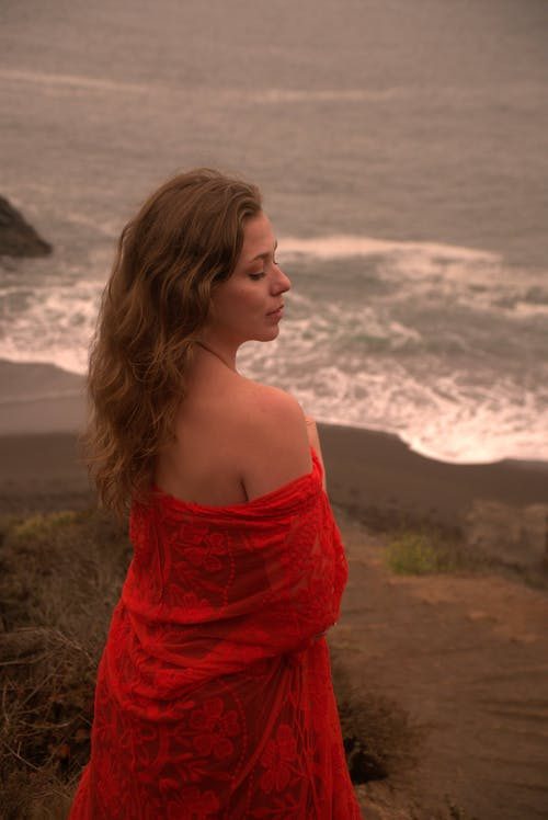 High angle back view of dreamy female with bare shoulders and closed eyes standing on seashore