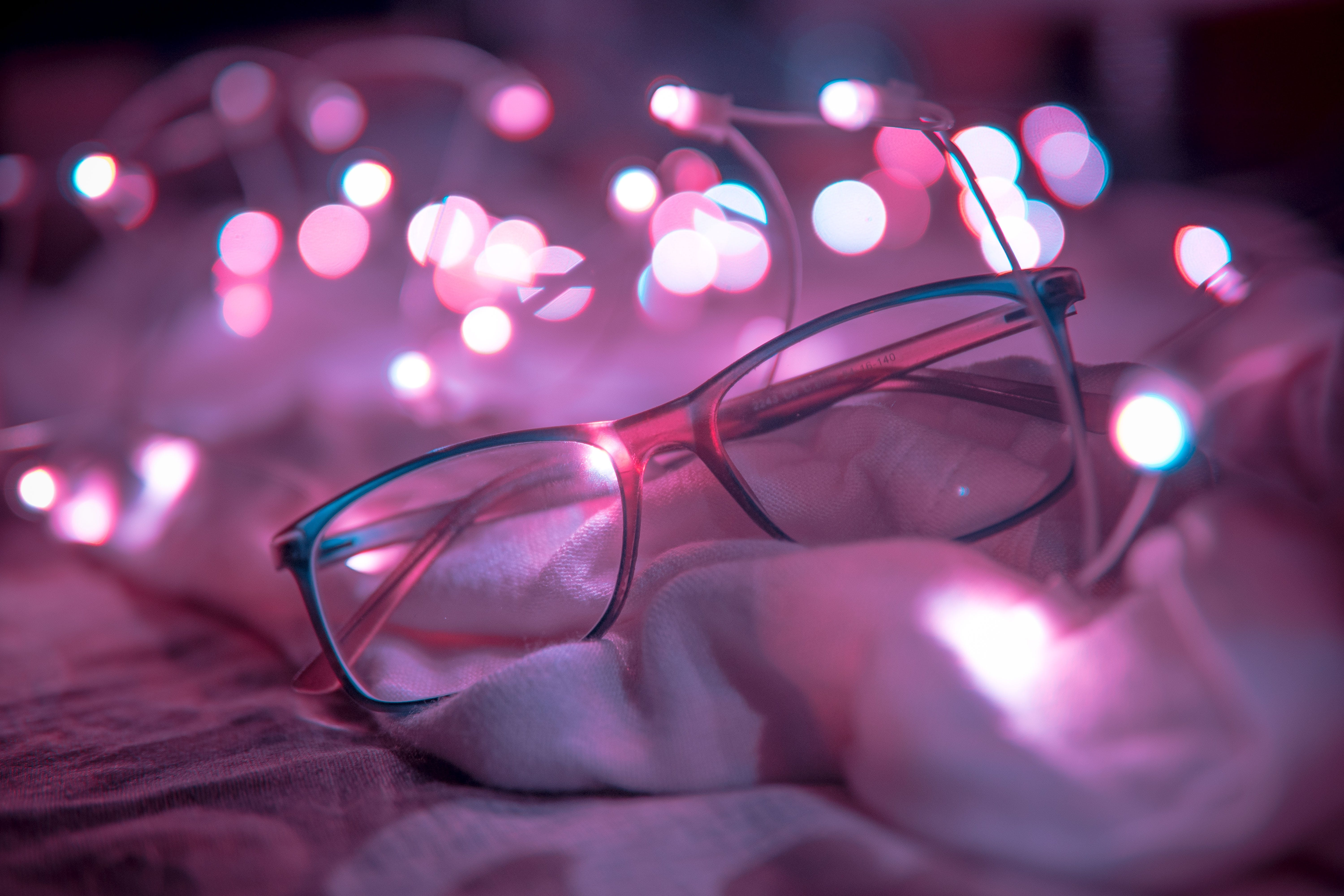 Shallow Focus Photography of Blue-framed Eyeglasses Near String Lights