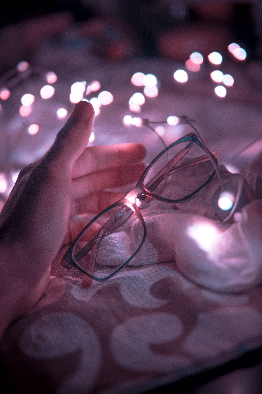 Black Frame Eyeglasses and White String Lights in White Textile