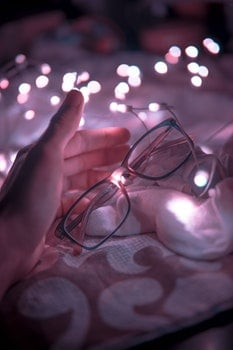 Black Frame Eyeglasses and White String Lights in White Textile
