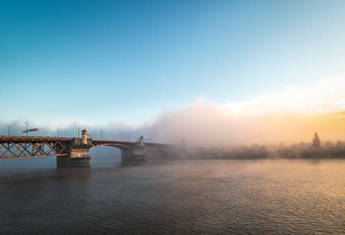 Magnificent scenery of famous Burnside Bridge crossing rippling river and hidden under fog against colorful sunset sky