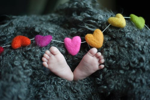Baby's Feet Covered With Black Wool Textile