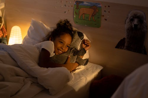 A Girl Lying on the Bed while Hugging a Stuffed Toy