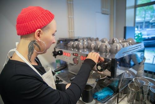 A Female Barista Using a Coffee Machine