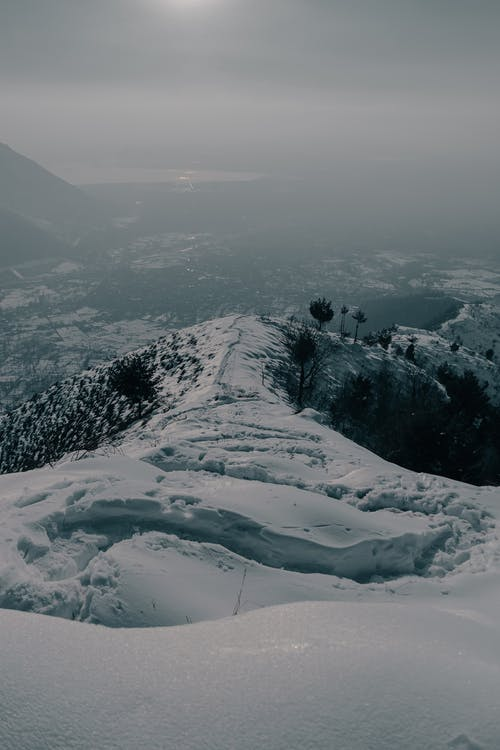 Scenery of snowy hill located in mountainous terrain covered with mist in gloomy day