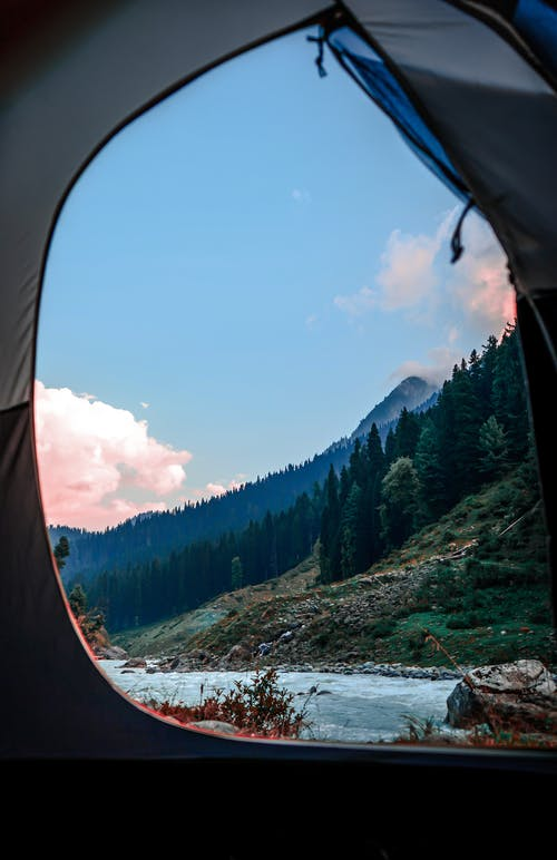 Camping tent on shore of rapid river in mountainous terrain