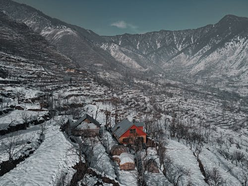 Small residential buildings among bare trees located in mountainous valley surrounded by rocky mountains covered with snow