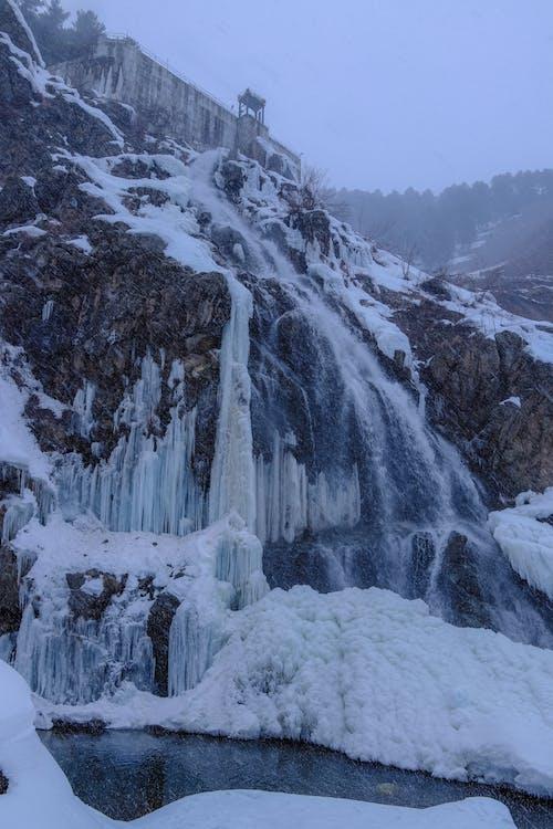 Frozen stream of water on rocky slope