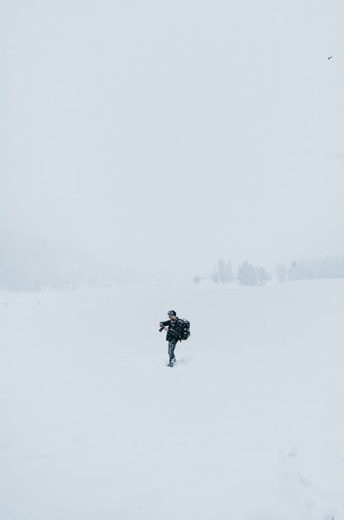 Male photographer standing in snowy valley