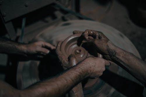 Crop artisans creating clay pot
