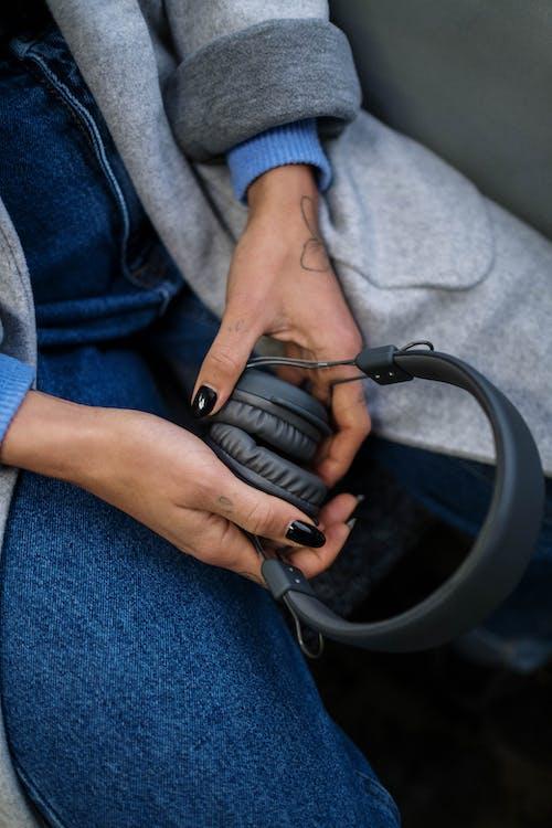 A Woman Holding a Wireless Headphone