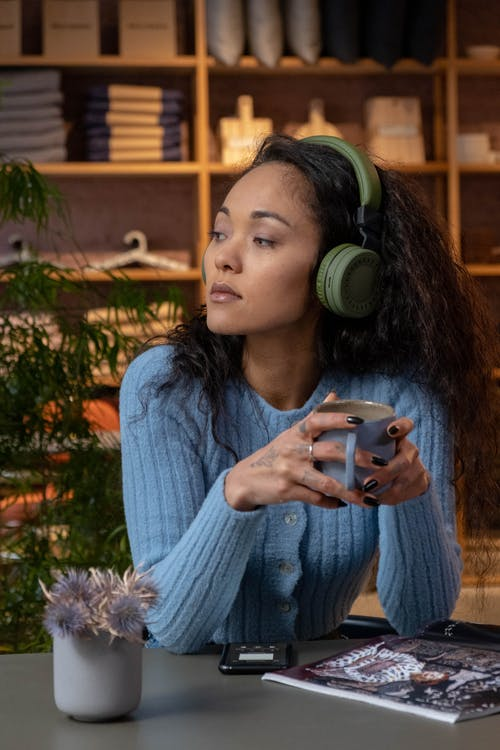 Woman in blue sweater listing to a podcast