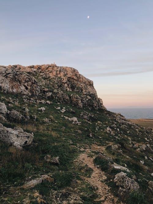 Rocky cliff on seashore near water