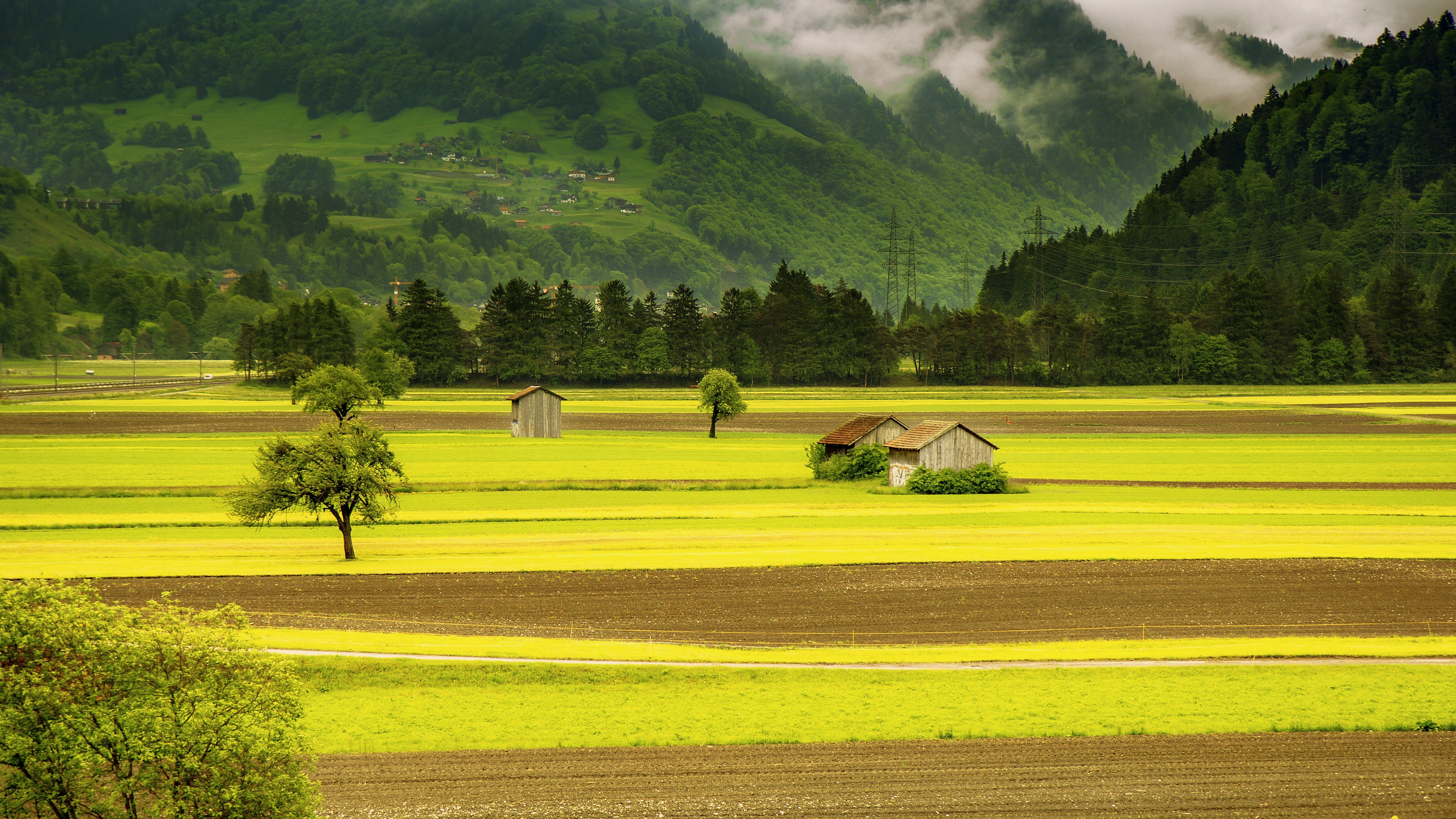 Brown House in the Middle of Green Field Grass Near Mountains