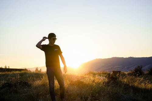 Man Standing on Grass Field Overlooking Sunrise