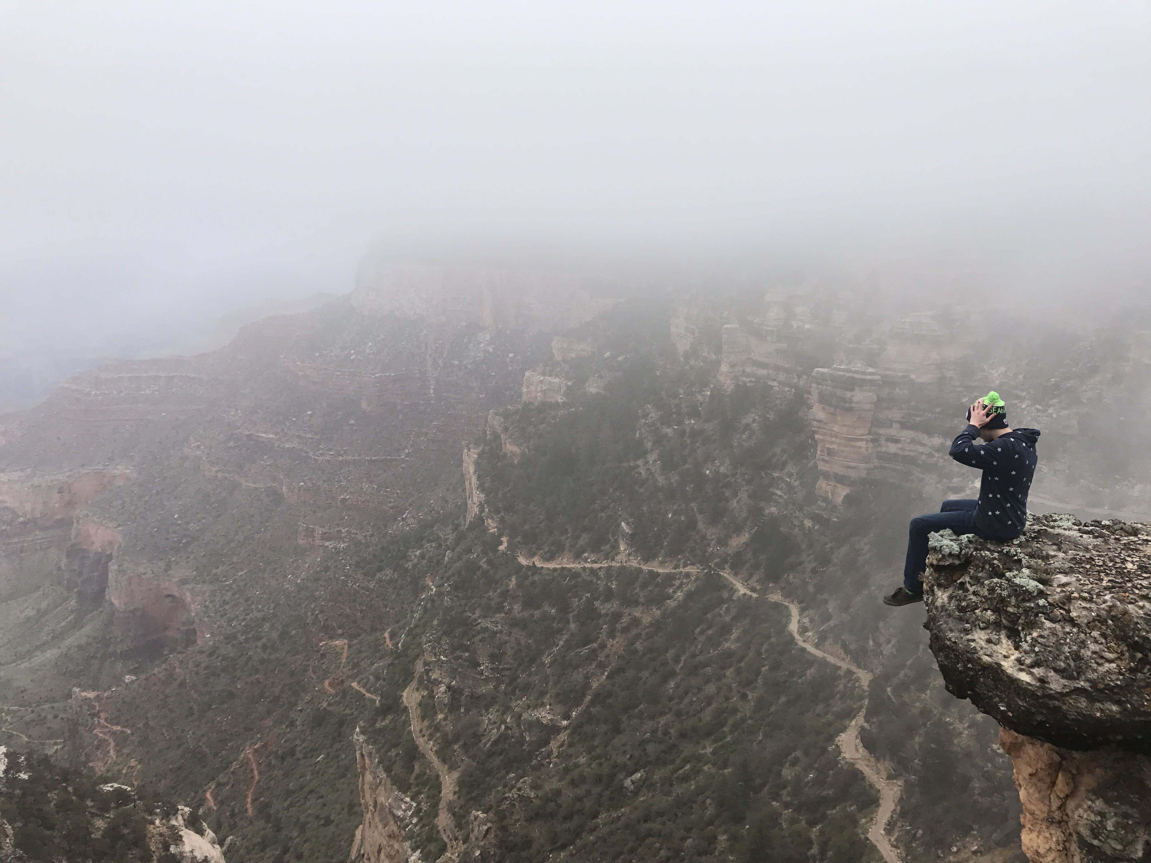 Man Sitting on Top of Cliff on Foggy Mountain