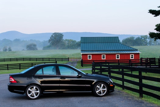 Black Coupe Near Black Wooden Fence during Daytime