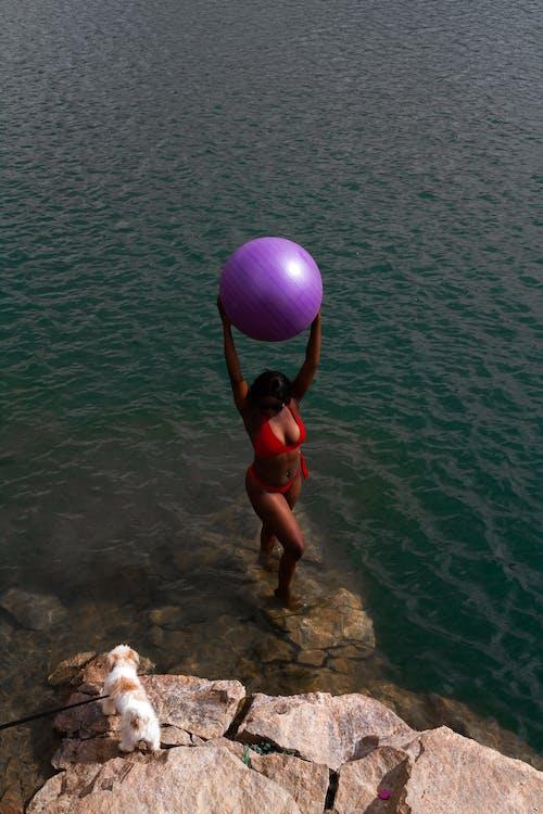 Woman in Red Bikini Holding Purple Balloon on Water